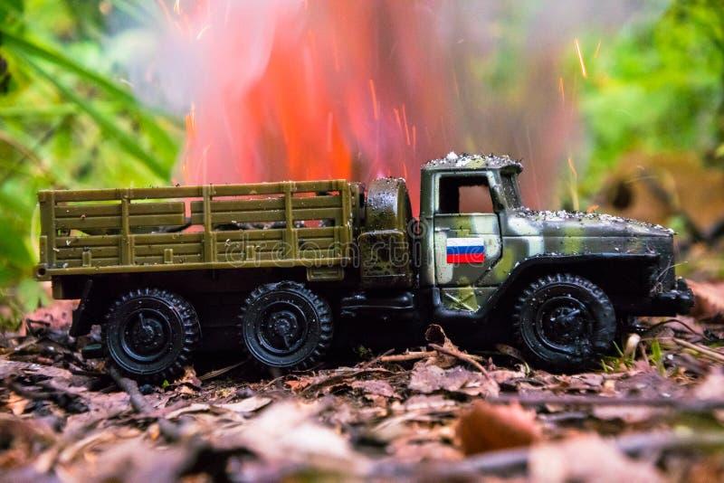 Het branden van een Russische militaire stuk speelgoed vrachtwagen Imitatie van onverwachte aanval stock fotografie