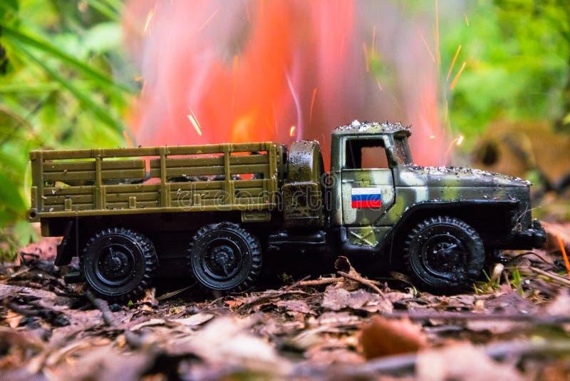 Het branden van een Russische militaire stuk speelgoed vrachtwagen Imitatie van onverwachte aanval stock foto's