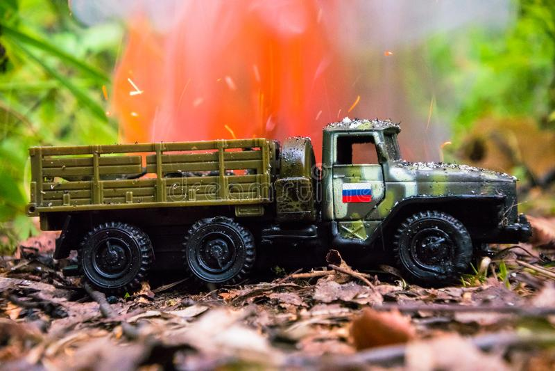 Het branden van een Russische militaire stuk speelgoed vrachtwagen Imitatie van onverwachte aanval stock afbeeldingen