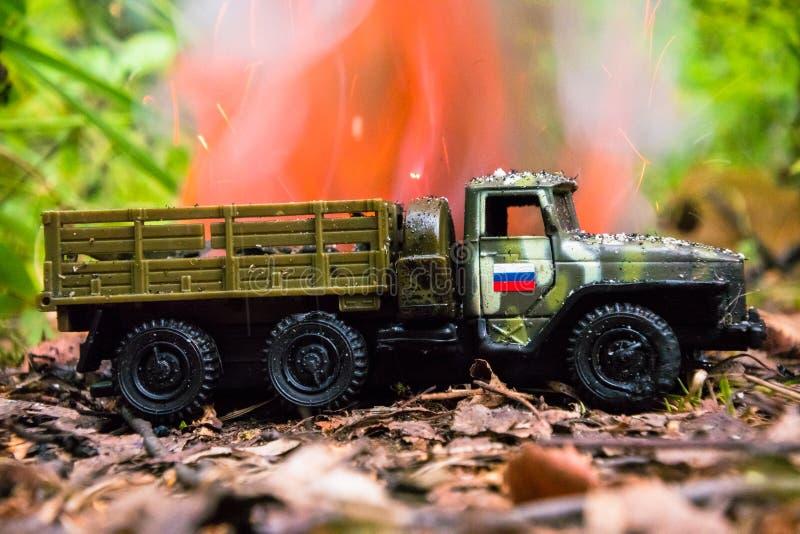 Het branden van een Russische militaire stuk speelgoed vrachtwagen Imitatie van onverwachte aanval royalty-vrije stock afbeelding