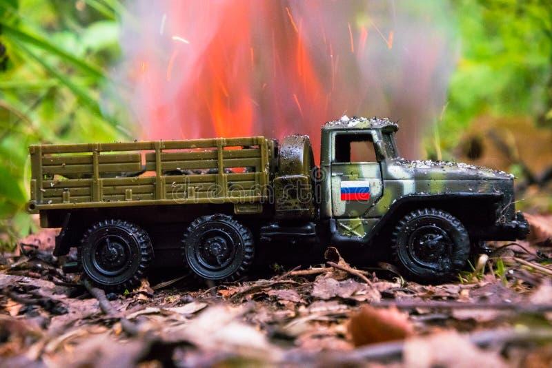 Het branden van een Russische militaire stuk speelgoed vrachtwagen Imitatie van onverwachte aanval royalty-vrije stock foto's
