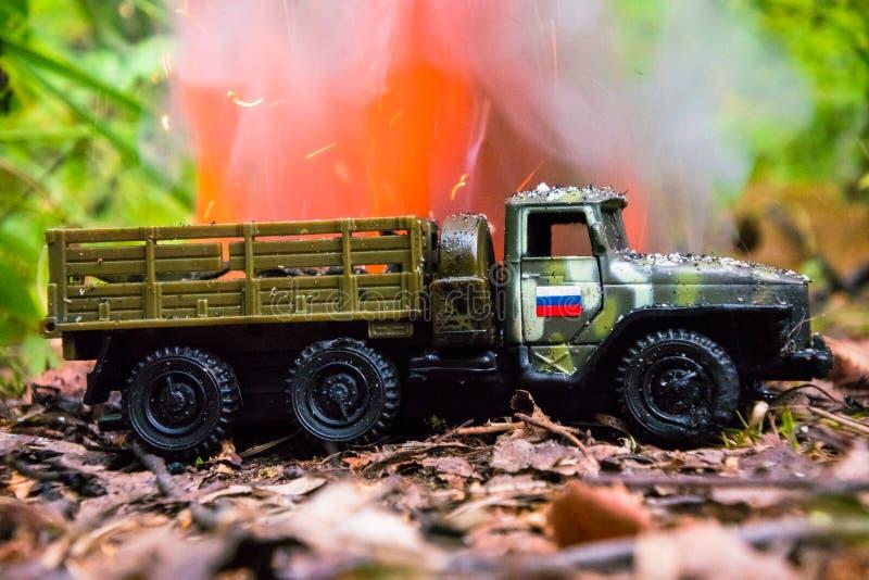 Het branden van een Russische militaire stuk speelgoed vrachtwagen Imitatie van onverwachte aanval stock afbeelding