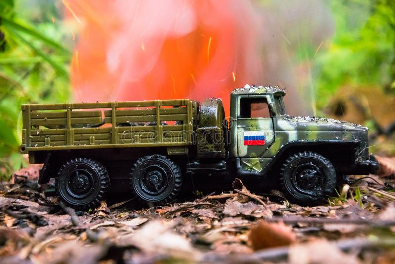 Het branden van een Russische militaire stuk speelgoed vrachtwagen Imitatie van onverwachte aanval royalty-vrije stock afbeeldingen