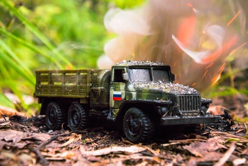 Het branden van een Russische militaire stuk speelgoed vrachtwagen Imitatie van onverwachte aanval royalty-vrije stock foto