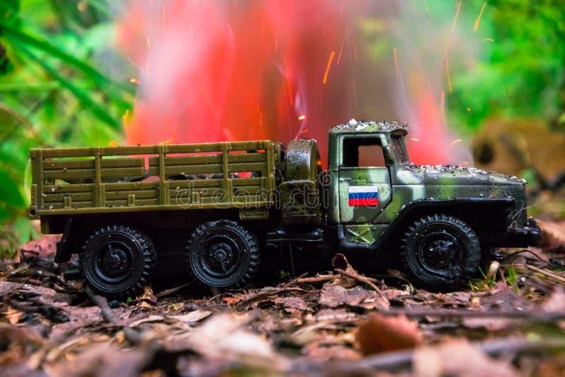 Het branden van een Russische militaire stuk speelgoed vrachtwagen Imitatie van onverwachte aanval stock foto