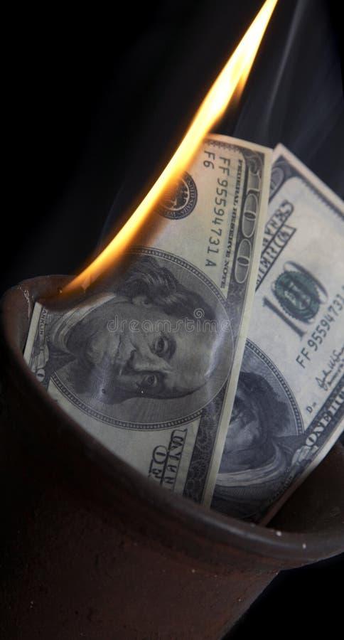 Het branden van geld stock fotografie