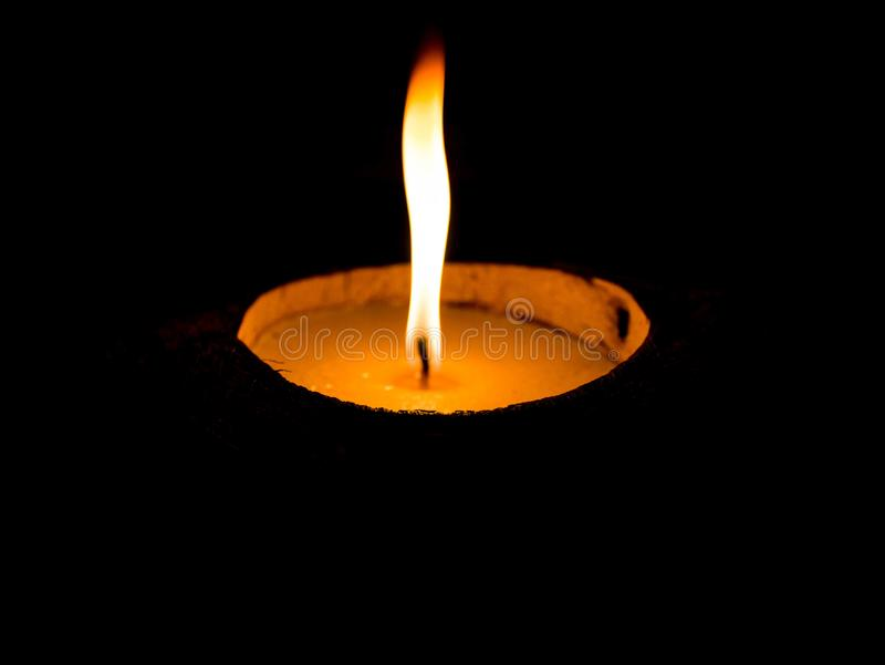 Het branden van gele kaars in het donkere close-up Een lichtgevende vlamkaarsen op een zwarte achtergrond stock foto