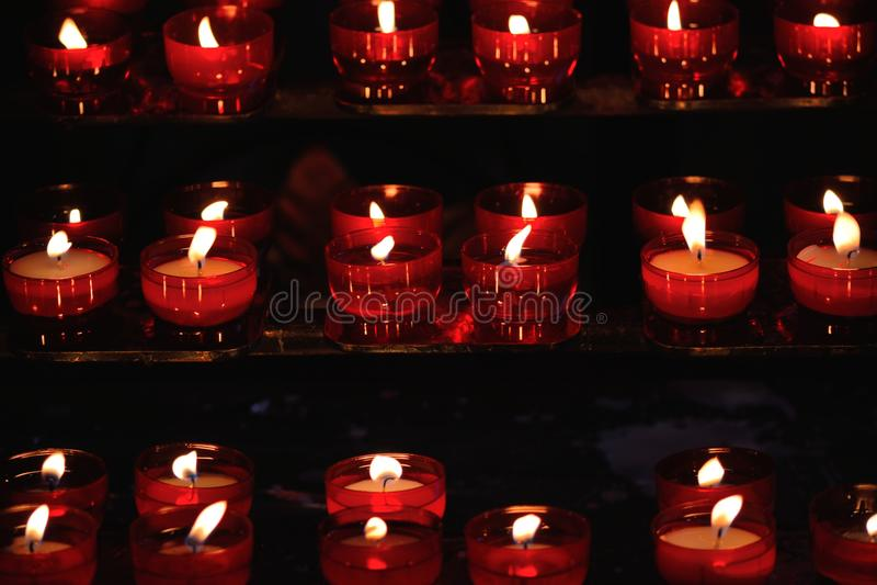 Het branden van rode kaarsen in een kerk stock afbeelding