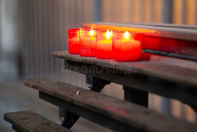 Het branden van rode kaarsen in een kerk in Barcelona stock afbeeldingen