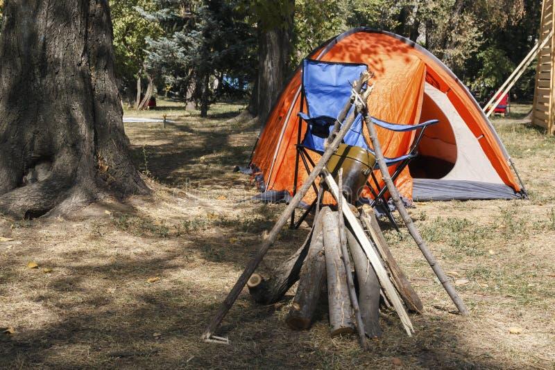 Het brandhout wordt gestapeld voor een brand dichtbij de tent, op een open plek in trek onder de bomen wordt geplaatst die stock afbeelding
