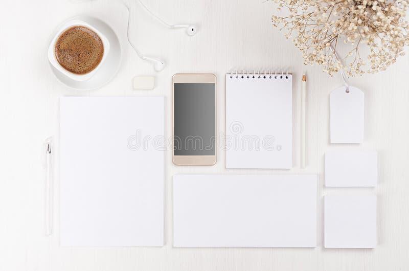Het brandmerken bedrijfsspot omhoog van witte lege kantoorbehoeftenreeks, telefoon, bloemen, koffiekop op lichte zachte witte hou royalty-vrije stock fotografie
