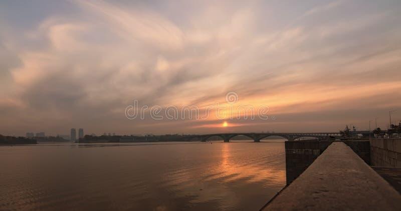 Het brede panorama van het hoeklandschap van Dnipro-Rivier, dijk en Merto-Brug Kleurrijke trillende die hemel in het water wordt  stock afbeeldingen