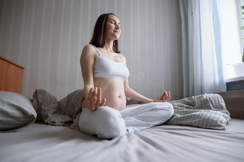 Het brede portret van de hoekbodem van het jonge zwangere vrouw ontspannen en het mediteren in bed stock foto's