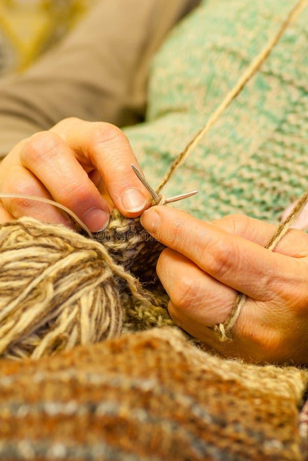 Het breien de scène van vrouwenhanden die een wol haken bekleedt en bruine bal van wol royalty-vrije stock afbeelding