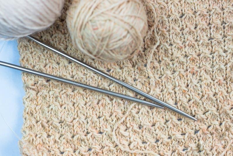 Het breien lopend project Een stuk van het breien met een bal van garen en het breien royalty-vrije stock afbeeldingen
