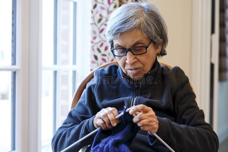 Het breien van de bejaarde stock foto
