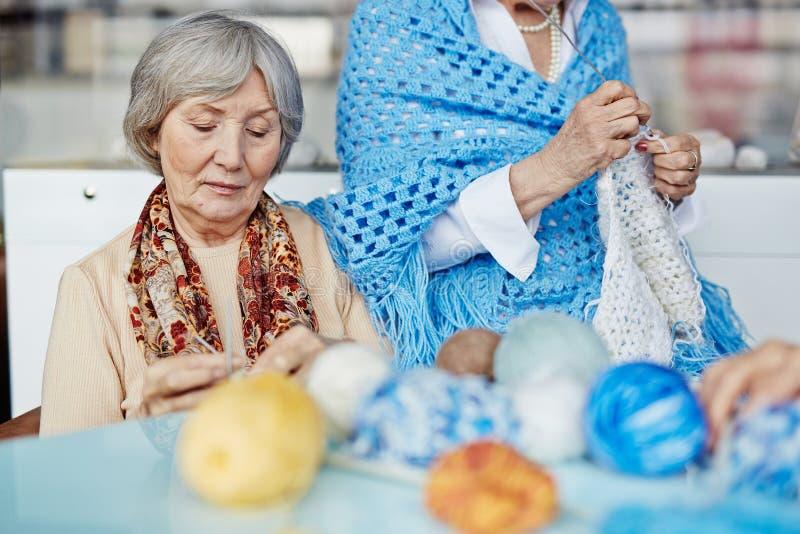Het breien van warme kleren met vriend royalty-vrije stock afbeelding