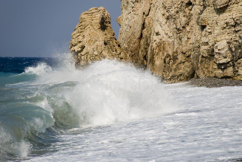 Het breken van de golf tegen rotsen royalty-vrije stock afbeeldingen