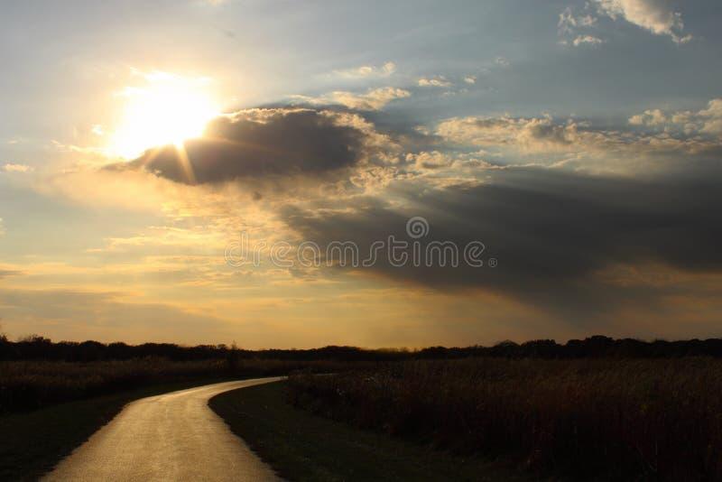 Het breken van de zon door wolken op een eenzame weg royalty-vrije stock foto