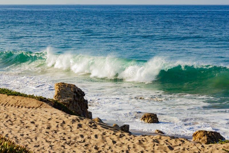 Het breken van transparante turkooise golf met terugslag en backspray op een zandig strand royalty-vrije stock afbeelding