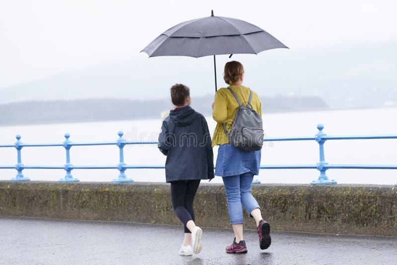 Het Britse natte weer van de de zomerparaplu met moeder en dochter royalty-vrije stock afbeeldingen