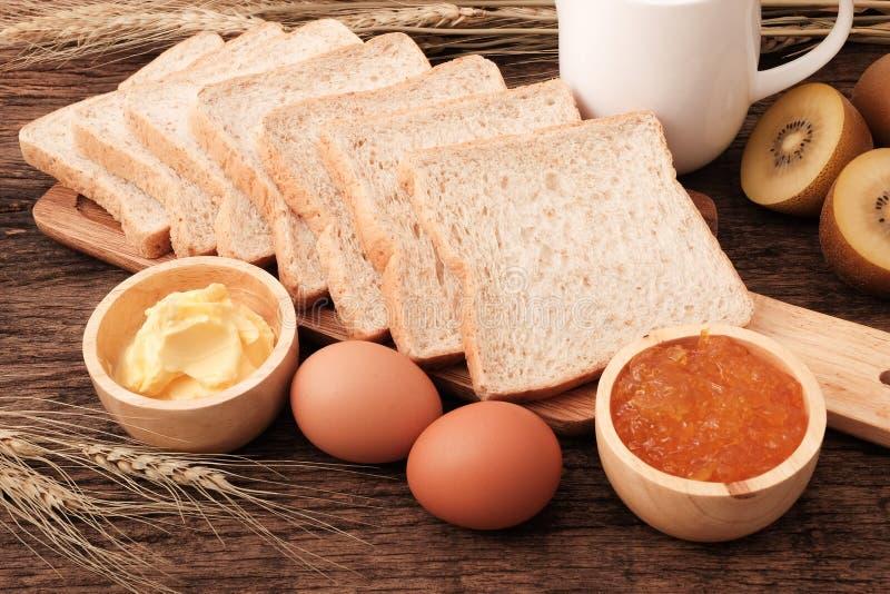 Het brood van de plak gehele tarwe, boter en oranje jam stock foto