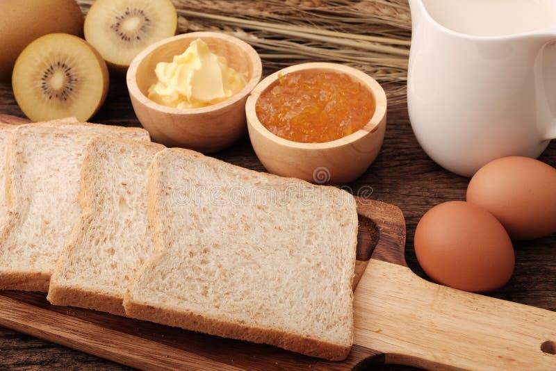 Het brood van de plak gehele tarwe, boter en oranje jam royalty-vrije stock fotografie