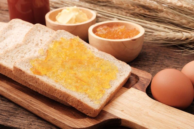 Het brood van de plak gehele tarwe, boter en oranje jam stock afbeeldingen
