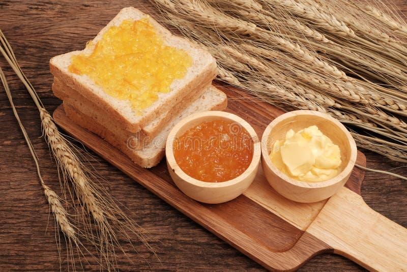 Het brood van de plak gehele tarwe, boter en oranje jam stock afbeelding