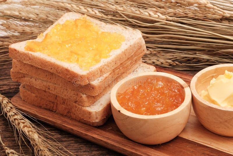 Het brood van de plak gehele tarwe, boter en oranje jam stock foto's