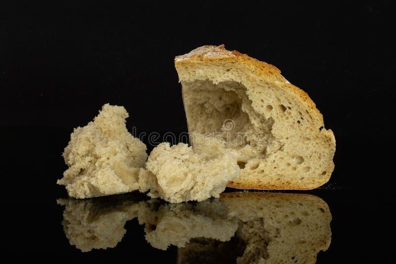Het brood van de roggetarwe op zwart glas wordt geïsoleerd dat stock afbeelding