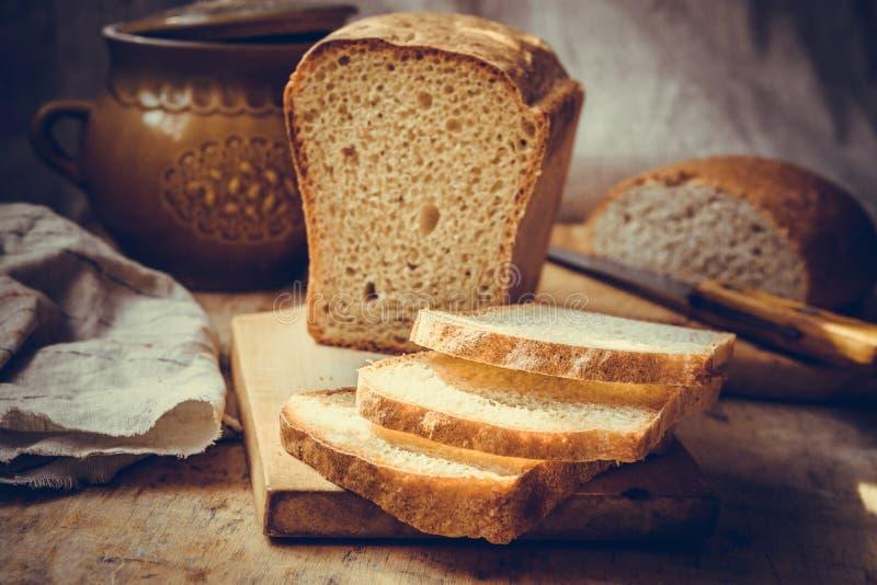 Het brood van het zuurdesembrood, op oude houten scherpe raad wordt gesneden, uitstekend aardewerk, linnenhanddoek, authentieke l stock fotografie