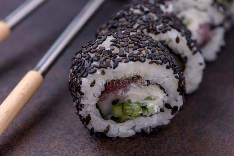 Het broodje van close-upsushi met zalm en zwarte sesam royalty-vrije stock afbeelding