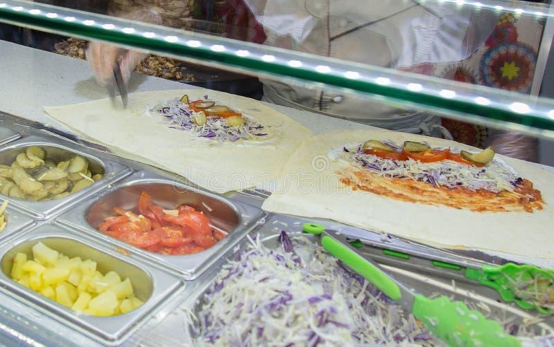 Het broodje van de Shawarmakip in een pitabroodje met verse groenten en room stock foto's