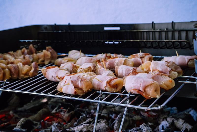 Het broodje van het grillbacon in BBQ met steenkool Gemarineerd vlees in metaal netto tijdens tuinpartij De zomerbarbecue in open stock foto's