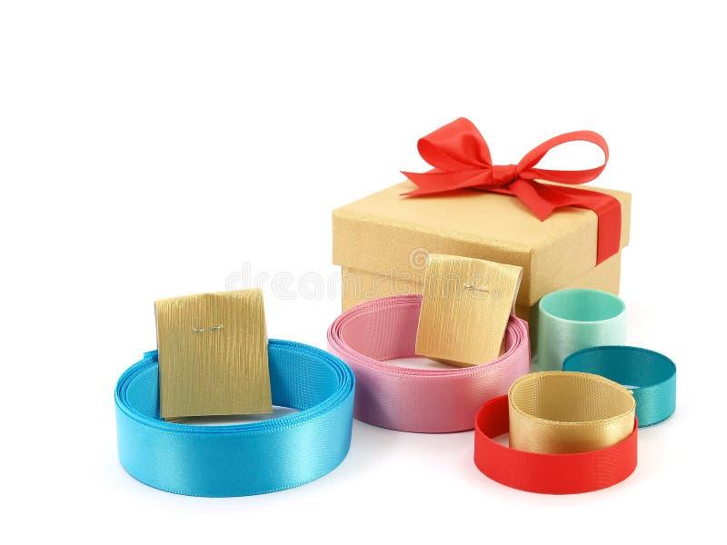 Het broodje van kleurrijke linten met gouden document etiketteert riemen en gouden giftvakje met rode die lintboog op witte achte stock fotografie
