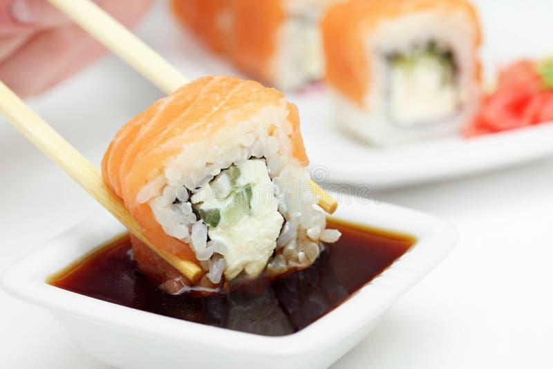 Het broodje van sushi in eetstokjes in sojasaus royalty-vrije stock foto