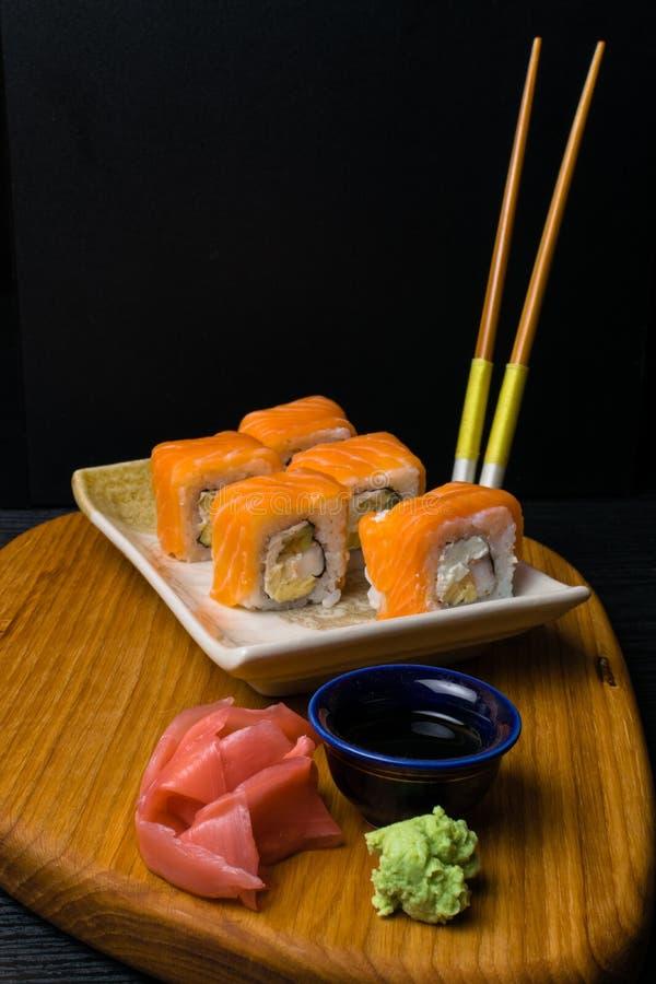 Het broodjessushi van Philadelphia met zalm, garnaal, roomkaas, sojasaus, gember, wasabi Japans voedsel met eetstokjes royalty-vrije stock foto