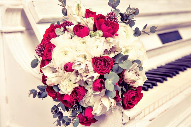 Het bruids boeket van rozen ligt op pianosleutels stock afbeeldingen