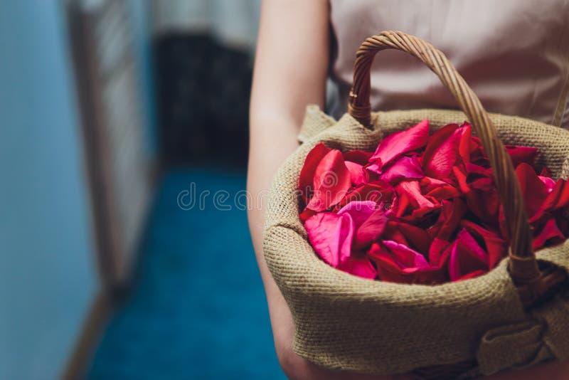 Het bruidsmeisje in een witte bloemmanden van de kledingsholding voor zich het verspreiden nam bloemblaadje bij een huwelijksontv royalty-vrije stock foto