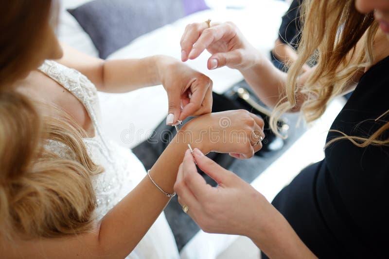Het bruidsmeisje helpt om een armband op zijn wapen voor de bruid te zetten stock foto