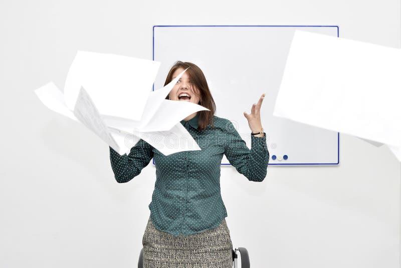 Het bruin-haired meisje in het bureau in woede wierp op documenten en documenten stock foto's
