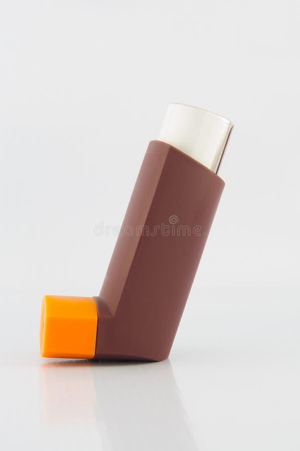 Bruin astmainhaleertoestel op witte achtergrond stock afbeeldingen