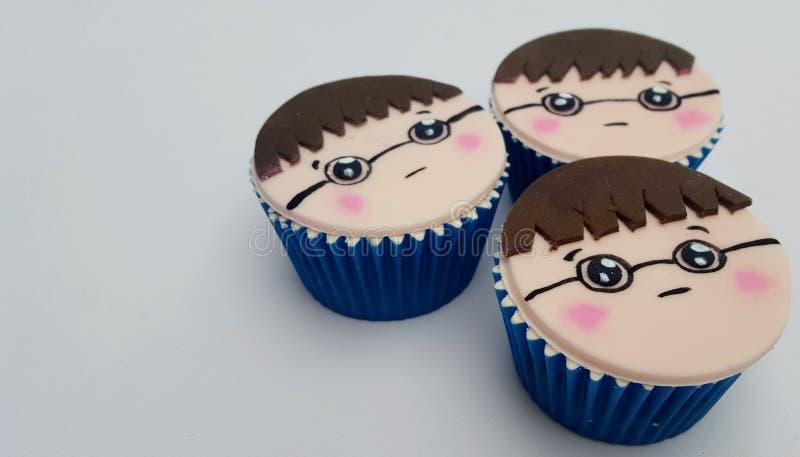 Het bruine haar van het jongensgezicht cupcakes met glazen stock afbeeldingen