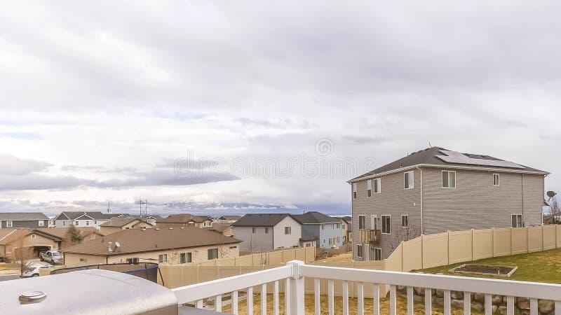 Het Bruine houten dek van het panoramakader met wit traliewerk die yardhuizen en bewolkte hemel overzien royalty-vrije stock afbeeldingen