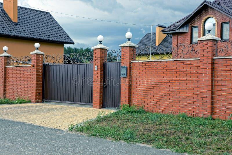 Het bruine ijzer sloot poorten en een deel van een lange baksteenomheining in de straat royalty-vrije stock foto