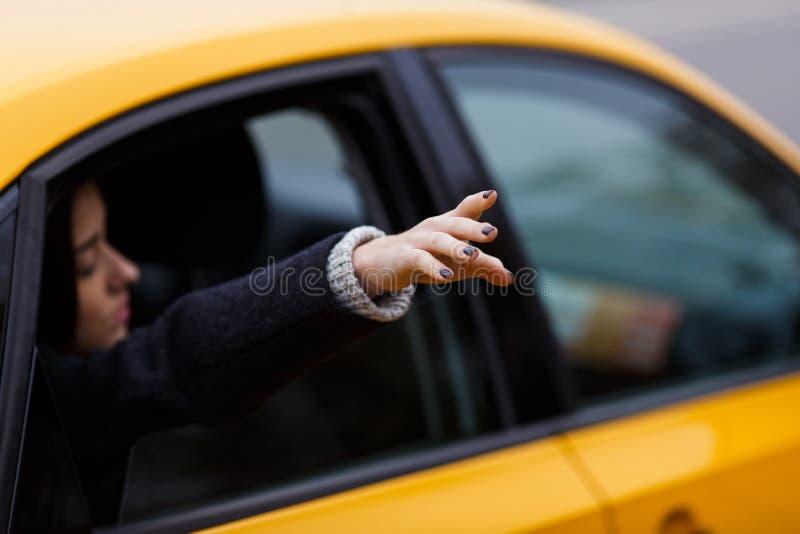 Het brunette breidt hand van taxi uit royalty-vrije stock foto