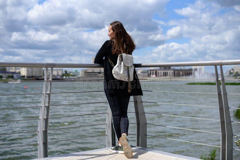 Het brunette met een rugzak bevindt zich op het observatiedek door het meer bewonderend de mening royalty-vrije stock foto's