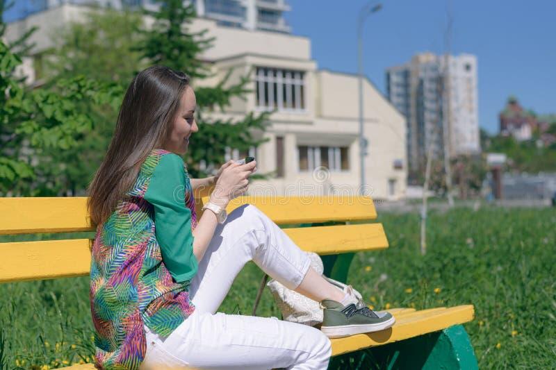 Het brunette met lang haar in witte jeans zit op een gele bank en geniet van smartphone, online mededeling, sociale netwerken, co royalty-vrije stock foto