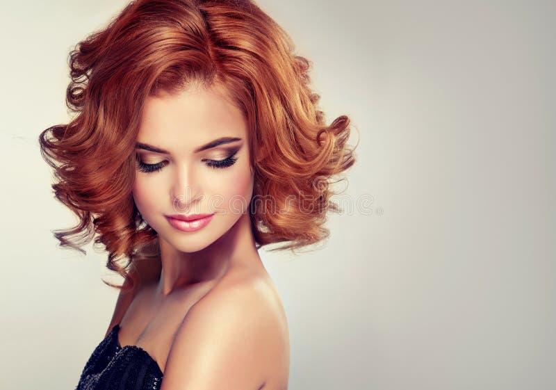 Het brunette met middenlengte gekruld haar en helder maakt omhoog stock foto